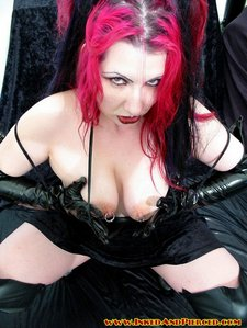 Scary looking gothic chick with pierced nipples spreading on the couch 09